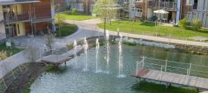Steeg mit Holzbelag, Teich mit Wasserspiel