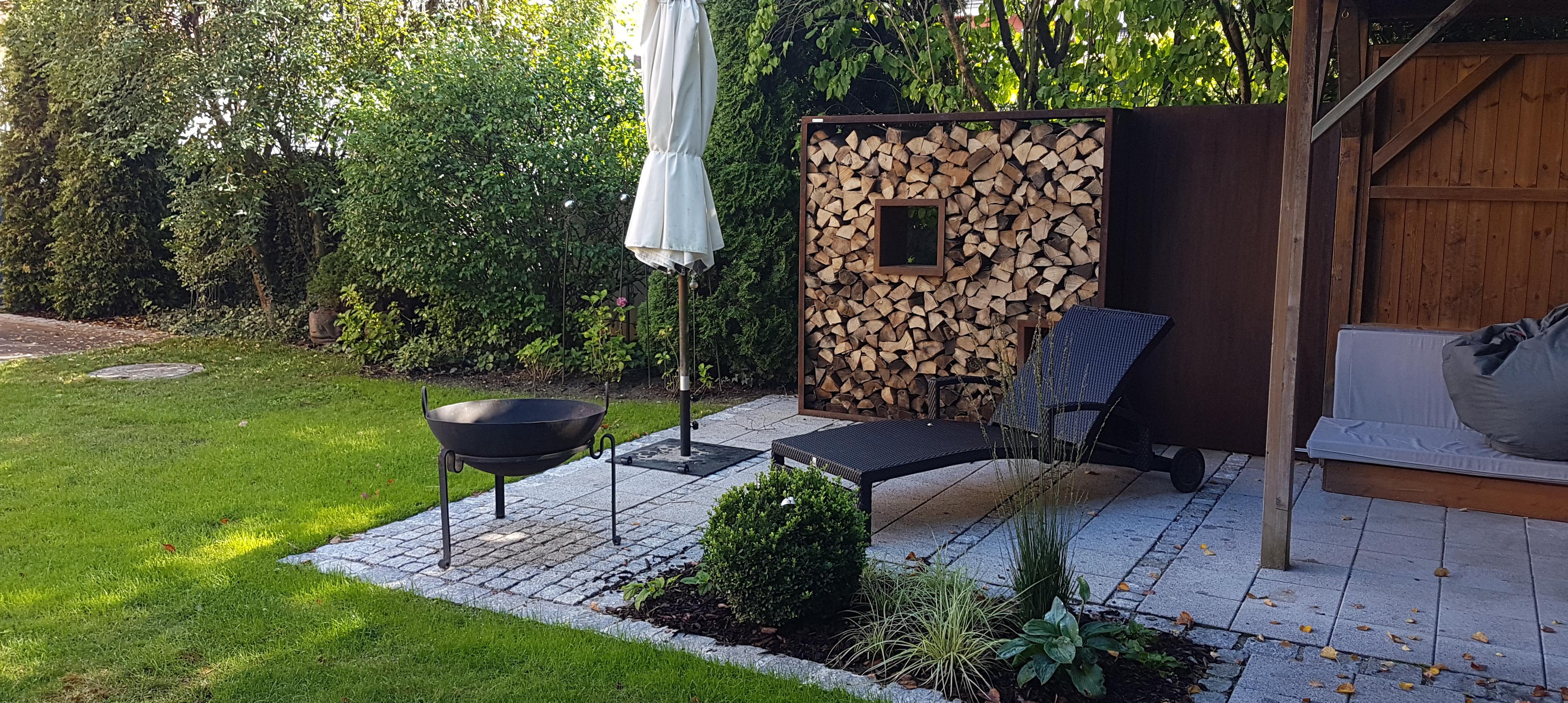 Sitzplatz mit Holzregal und Feuerschale